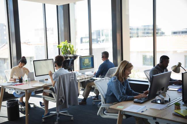 Groupe multi-ethnique de collègues masculins et féminins travaillant dans un bureau moderne, assis à des bureaux, utilisant des ordinateurs, portant des écouteurs et parlant — Photo de stock