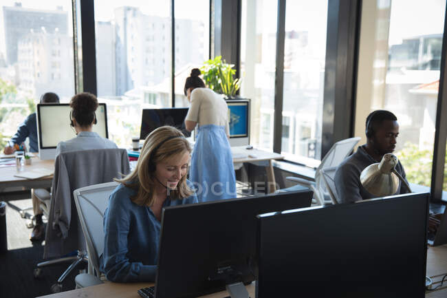 Многонациональная группа коллег-мужчин и женщин, работающих в современном офисе, сидящих за письменными столами, пользующихся компьютерами, в наушниках и разговаривающих — стоковое фото