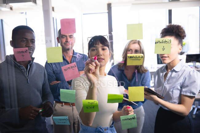 Un groupe diversifié de gens d'affaires travaillant dans un bureau moderne, remue-méninges écrit sur un tableau clair avec des notes de service, vu à travers — Photo de stock
