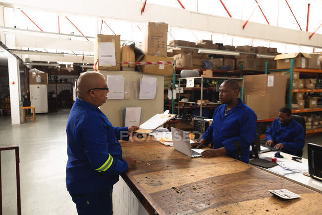 A mixed race male supervisor and an African American male worker in a storage warehouse at a factory making wheelchairs, standing and talking at a workbench — Stock Photo
