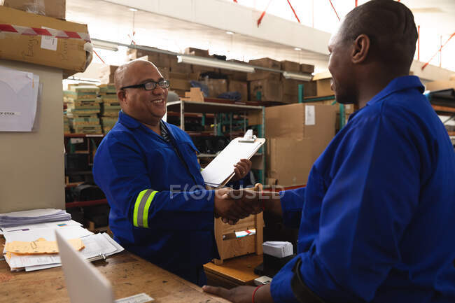 A mixed race male supervisor and an African American male worker in a storage warehouse at a factory making wheelchairs, shaking hands and talking at a workbench — Stock Photo
