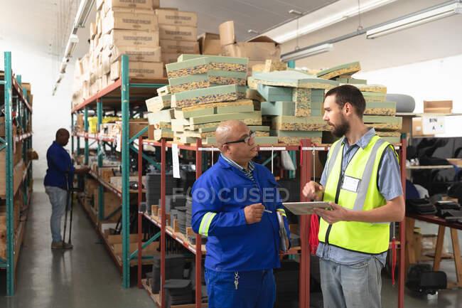 Чоловічий і кавказький наглядач на складі на фабриці роблять інвалідні візки, стоять і розмовляють, тримаючи табличку. — стокове фото