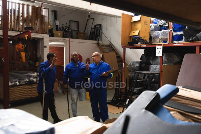 Three of Caucasian and African American male workers in a storage warehouse at a factory making wheelchairs, standing and talking, two of them are disabled and using crutches — Stock Photo