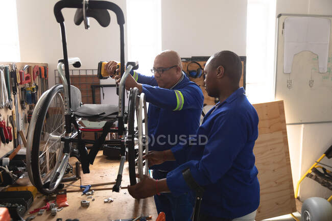 African American and mixed race male workers in a workshop at a factory making wheelchairs, standing at a workbench and assembling parts of a product — Stock Photo