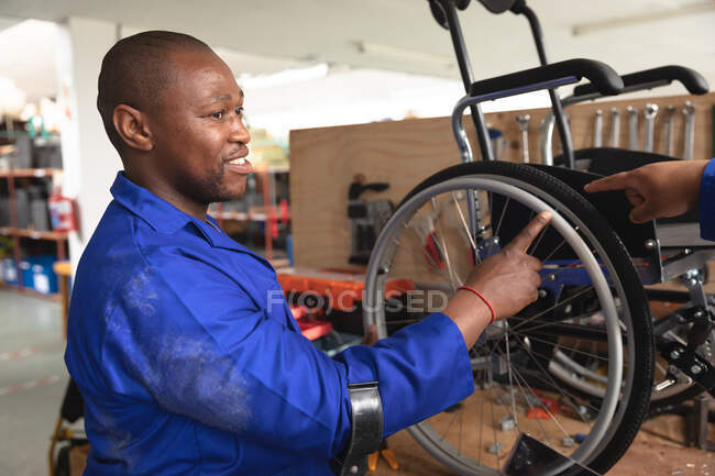 An African American male worker in a workshop at a factory making wheelchairs, standing at a workbench and assembling parts of a product — Stock Photo