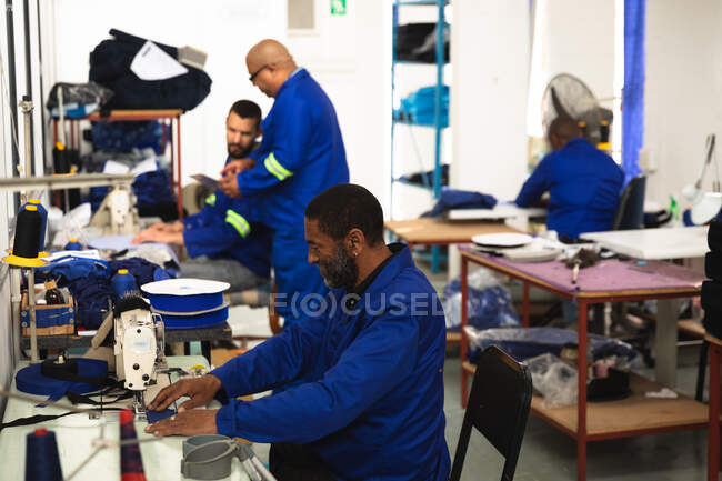 An African American male worker in a workshop at a factory making wheelchairs, sitting at a workbench, using a sewing machine, with other workers working in the background — Stock Photo