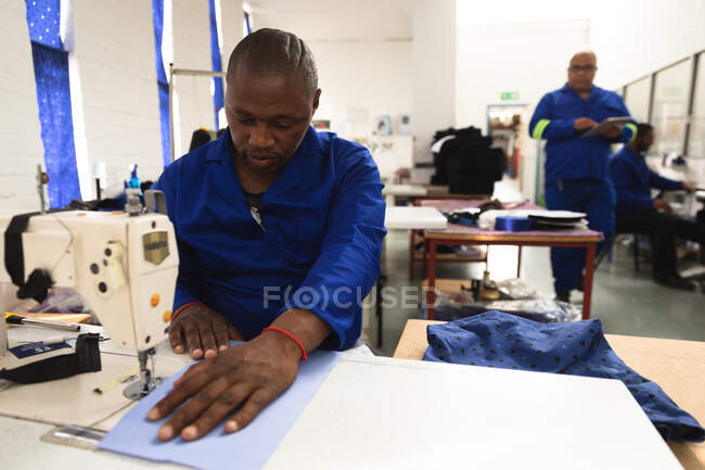 An African American male worker in a workshop at a factory making wheelchairs, sitting at a workbench, using a sewing machine — Stock Photo