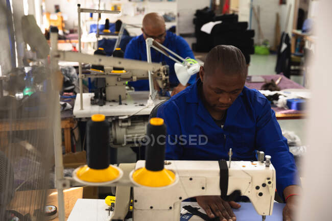 Многонациональная группа рабочих-мужчин в мастерской на фабрике по производству инвалидных колясок, сидящих на рабочем месте, используя швейную машинку — стоковое фото