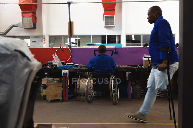 Disabled African American male worker in a workshop at a factory making wheelchairs, sitting at a workbench assembling parts of a product, sitting in wheelchair, a colleague walking past on crutches — Stock Photo