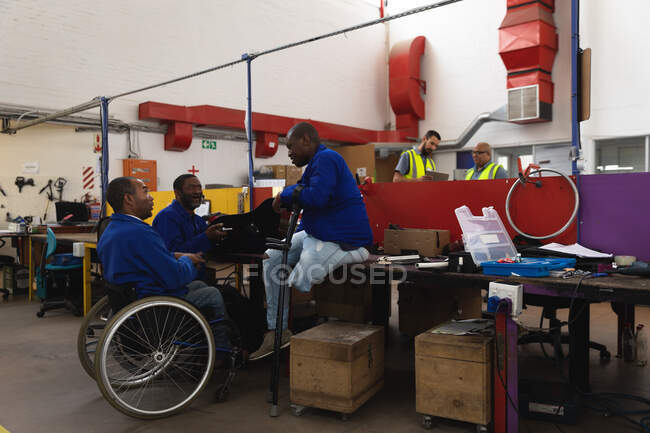 Group of disabled African American male workers in a workshop at a factory making wheelchairs, sitting at a workbench assembling parts of a product, one sitting in a wheelchair, one using crutches — Stock Photo