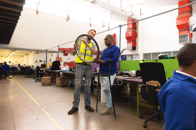 An African American male worker and a Caucasian male supervisor in the workshop at a factory making wheelchairs, standing and inspecting a wheel together, wearing a workwear — Stock Photo