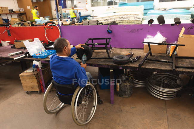 Disabled African American male worker in a workshop at a factory making wheelchairs, sitting at a workbench assembling parts of a product, sitting in wheelchair — Stock Photo