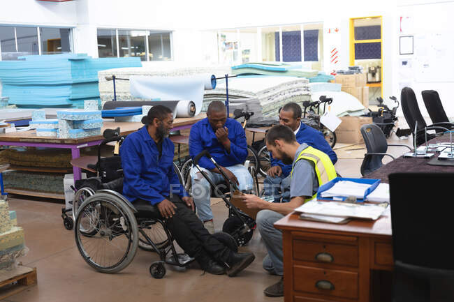 Group of disabled African American male workers sitting in wheelchairs and a Caucasian supervisor in a workshop at a factory making wheelchairs, talking, supervisor holding a clipboard — Stock Photo