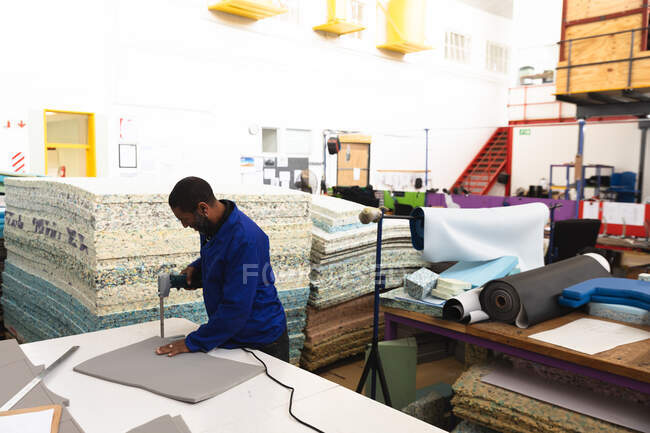 An African American male worker in a workshop at a factory making wheelchairs, standing at a workbench, cutting sheets of foam with an electric hand tool — Stock Photo