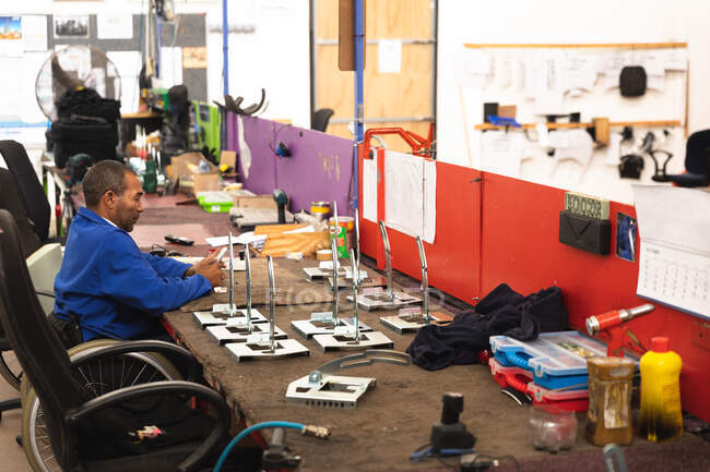 A disabled African American male worker in a workshop at a factory making wheelchairs, sitting at a workbench assembling parts of a product, sitting in wheelchair — Stock Photo