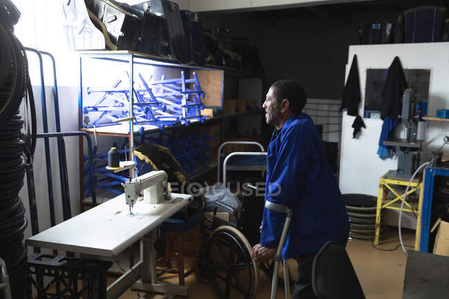 A disabled African American male worker standing on crutches, wearing workwear, in a storage warehouse at a factory making wheelchairs, inspecting parts — Stock Photo