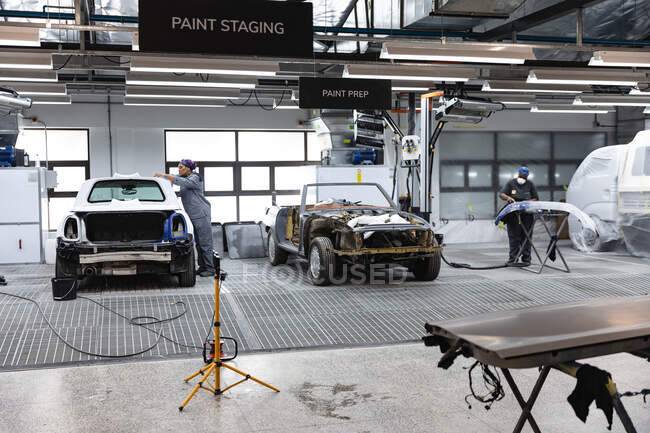 Two African American male car mechanics working on car repairs in a township workshop, one working on a car roof the other painting a front body panel — Stock Photo