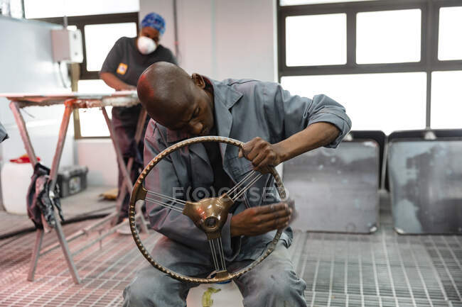 An African American male car mechanic working in a township workshop, sitting and polishing a car steering wheel, with a colleague wearing a breathing mask working in the background — Stock Photo