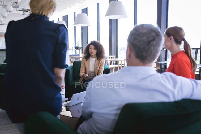 Groupe multi-ethnique de collègues masculins et féminins travaillant dans un bureau moderne, se réunissant dans un salon pour discuter des affaires et de leur travail — Photo de stock