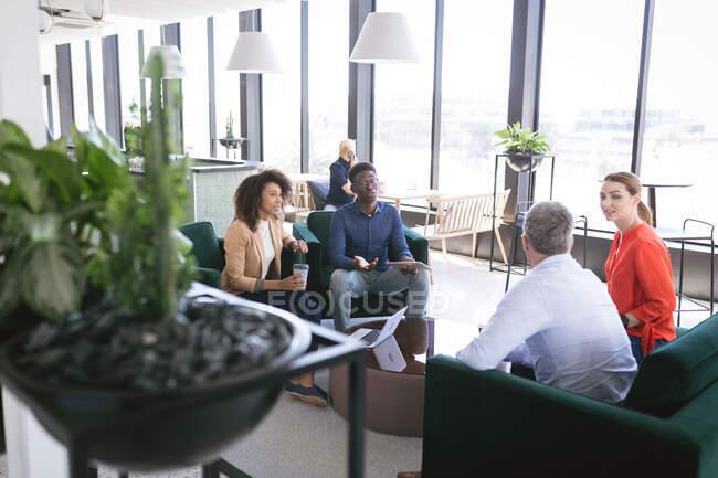 Gruppo multietnico di colleghi di sesso maschile e femminile che lavorano in un ufficio moderno, riuniti in un'area lounge per discutere di affari e del loro lavoro — Foto stock