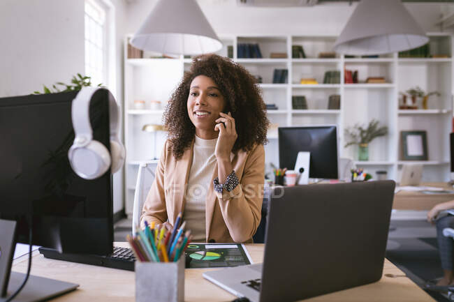 Деловая женщина смешанной расы, работающая в современном офисе, сидящая за столом и за компьютером, разговаривающая на смартфоне, со своими коллегами по бизнесу, работающими на заднем плане — стоковое фото