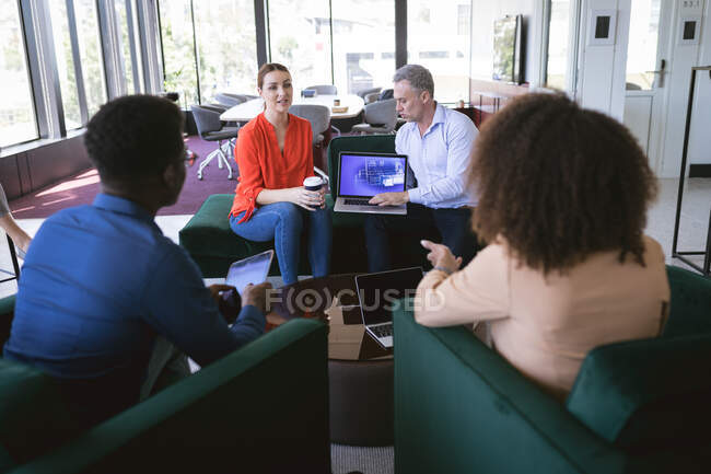 Groupe multiethnique de collègues d'affaires masculins et féminins travaillant dans un bureau moderne, se réunissant dans un salon pour discuter de leur travail — Photo de stock
