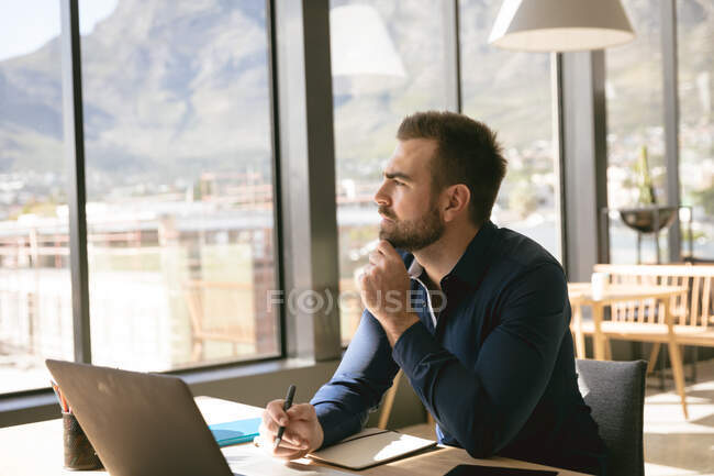 A Caucasian businessman working in a modern office, sitting at a desk and using a laptop computer, holding a pen, looking away and thinking — Stock Photo