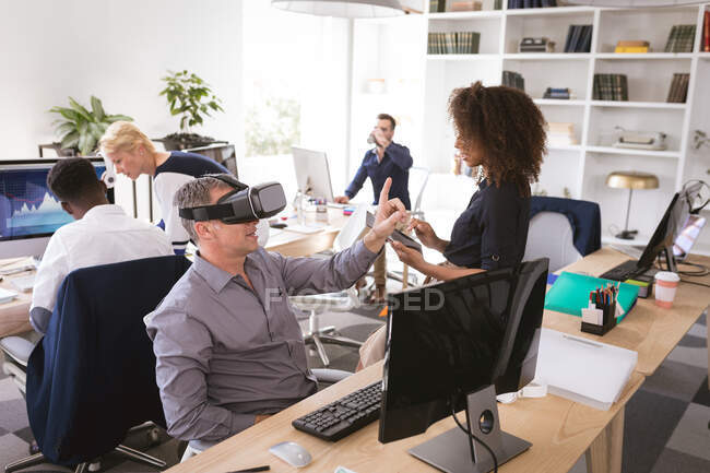 A Caucasian businessman working in a modern office, wearing a VR headset and touching virtual interactive screen, with his business colleagues working at desks in the background — Stock Photo