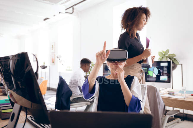 A Caucasian businesswoman working in a modern office, wearing VR headset, touching virtual interactive screen, with her business colleagues working in the background — Stock Photo