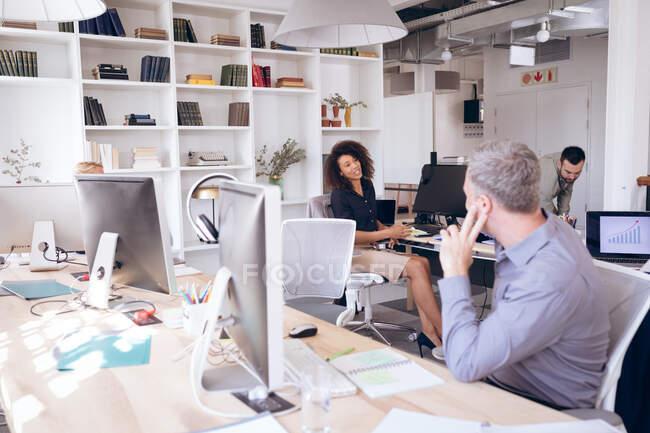 Gruppo multietnico di colleghi uomini e donne che lavorano in un ufficio moderno, seduti alla scrivania, usando i computer, discutendo del loro lavoro — Foto stock