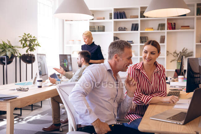 A Caucasian businesswoman and businessman working in a modern office, using a laptop computer and talking, with their business colleagues working in the background — Stock Photo