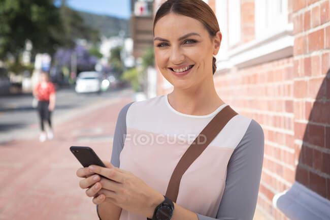 Портрет кавказской деловой женщины в солнечный день, держащей и использующей смартфон, смотрящей в камеру и улыбающейся — стоковое фото