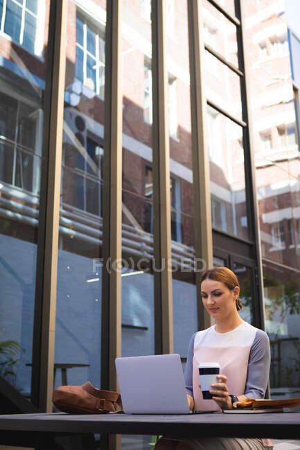 Кавказская деловая женщина в солнечный день сидит за столом, держит кофе на вынос и пользуется ноутбуком — стоковое фото