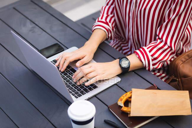 Деловая женщина на ходу в солнечный день, сидя за столом и работая над ноутбуком, с кофе на вынос на столе — стоковое фото