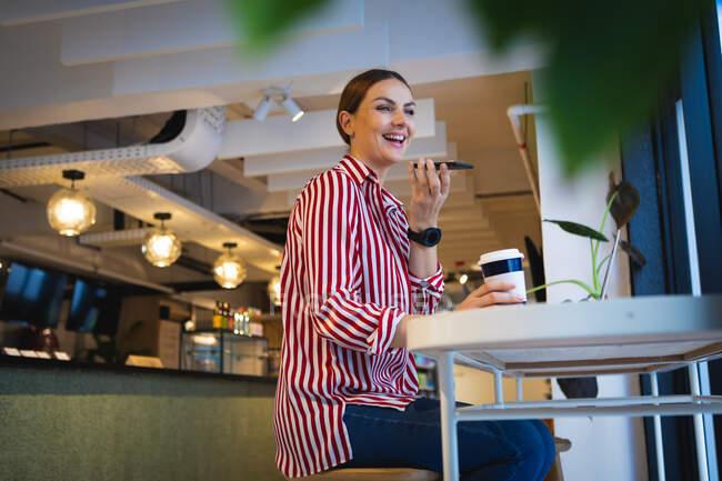 Кавказская деловая женщина делает телефонный звонок, держа перед собой смартфон, сидя за столом в кафе — стоковое фото
