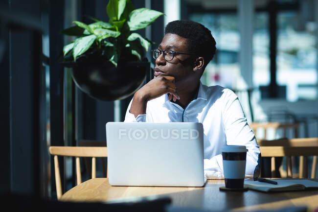 Афро-американский бизнесмен, сидящий за столом в кафе, работающий над ноутбуком и думающий, с чашкой кофе на столе — стоковое фото