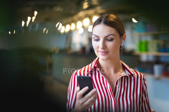 Кавказская деловая женщина с короткими волосами, стоящая в кафе, держащая перед собой смартфон, одетая в модную одежду — стоковое фото
