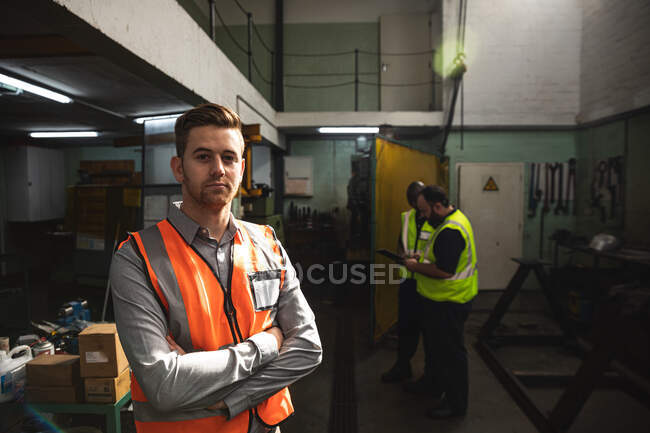 Portrait of a Caucasian male factory worker wearing a high vis vest looking at camera with arms crossed, with colleagues in the background. Workers in industry at a factory making hydraulic equipment. — Stock Photo