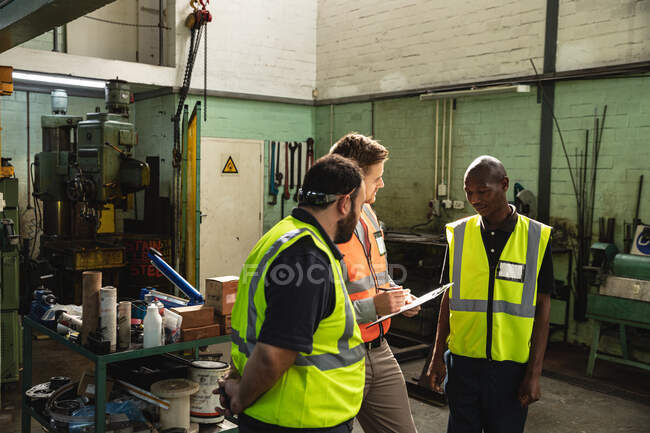 Two Caucasian and an African American male factory workers wearing a high vis vest talking and holding clipboard. Workers in industry at a factory making hydraulic equipment. — Stock Photo