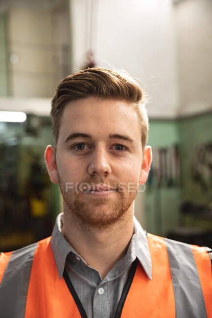 Portrait of a Caucasian male factory worker wearing a high vis vest looking at camera and smiling. — Stock Photo