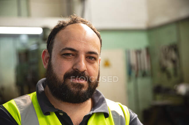 Portrait of a Caucasian male factory worker wearing a high vis vest looking at camera. — Stock Photo