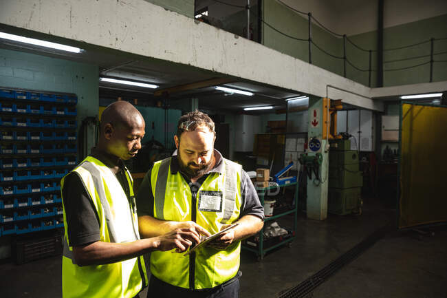 African American and Caucasian male factory workers wearing a high vis vest talking and using tablet. Workers in industry at a factory making hydraulic equipment. — Stock Photo