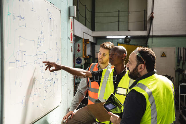 Two Caucasian and an African American male factory workers wearing a high vis vest holding tablet and looking at plans on a board. Workers in industry at a factory making hydraulic equipment. — Stock Photo