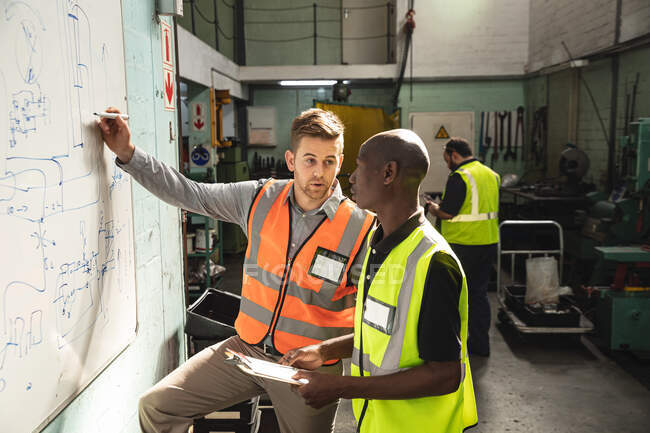 Caucasian and African American male factory workers wearing a high vis vest holding clipboard and writing on a board, talking. Workers in industry at a factory making hydraulic equipment. — Stock Photo