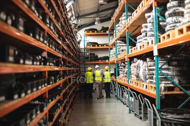 Двое белых и афроамериканец, работающие на фабрике, в бронежилете и проверяющих. Промышленные рабочие на заводе по производству гидравлического оборудования. — стоковое фото