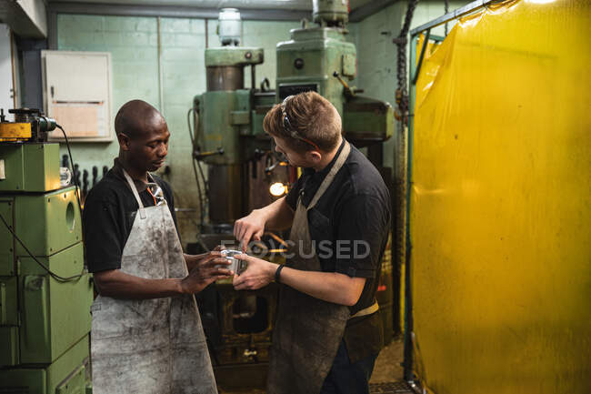 African American and Caucasian male factory workers wearing apron, talking and holding hydraulic part. Workers in industry at a factory making hydraulic equipment. — Stock Photo