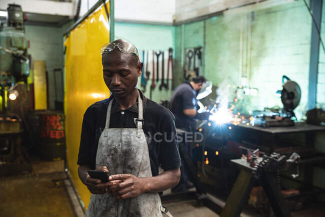African American male factory worker wearing apron using smartphone with coworker welding in the background. Workers in industry at a factory making hydraulic equipment. — Stock Photo