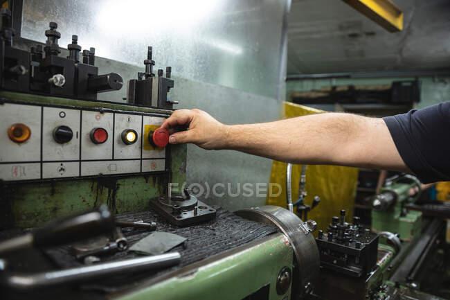 Arm eines männlichen Fabrikarbeiters in einer Fabrik, Knopfdruck und Einschalten der Maschine. — Stockfoto