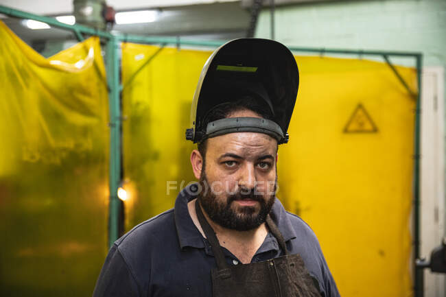 Portrait of a Caucasian male factory worker wearing dark apron and welding mask, looking at camera. — Stock Photo