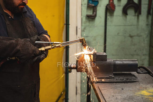 Caucasian male factory worker wearing dark apron and safety gloves, standing at a workbench and welding. — Stock Photo